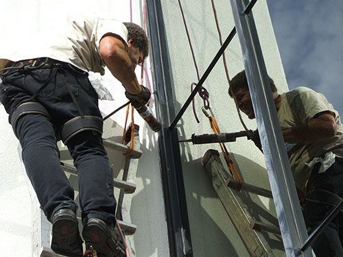 Man sealing high rise building window