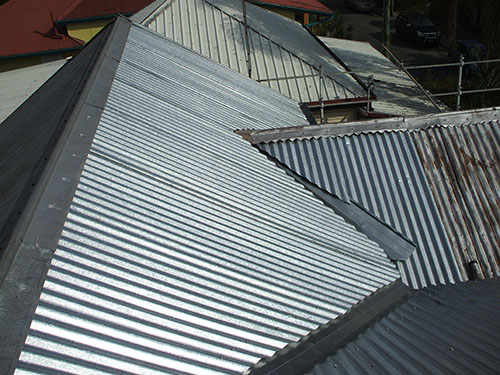 Restored metal roof surrounded by rusty ones